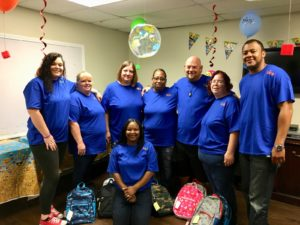 Sapulpa-Tulsa team pose with backpacks filled with school supplies