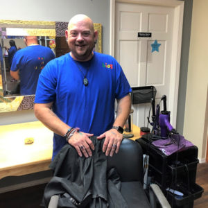 Sam Markcum, part-time direct support professional, with barber chair