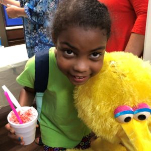 child poses with a snowcone and Big Bird