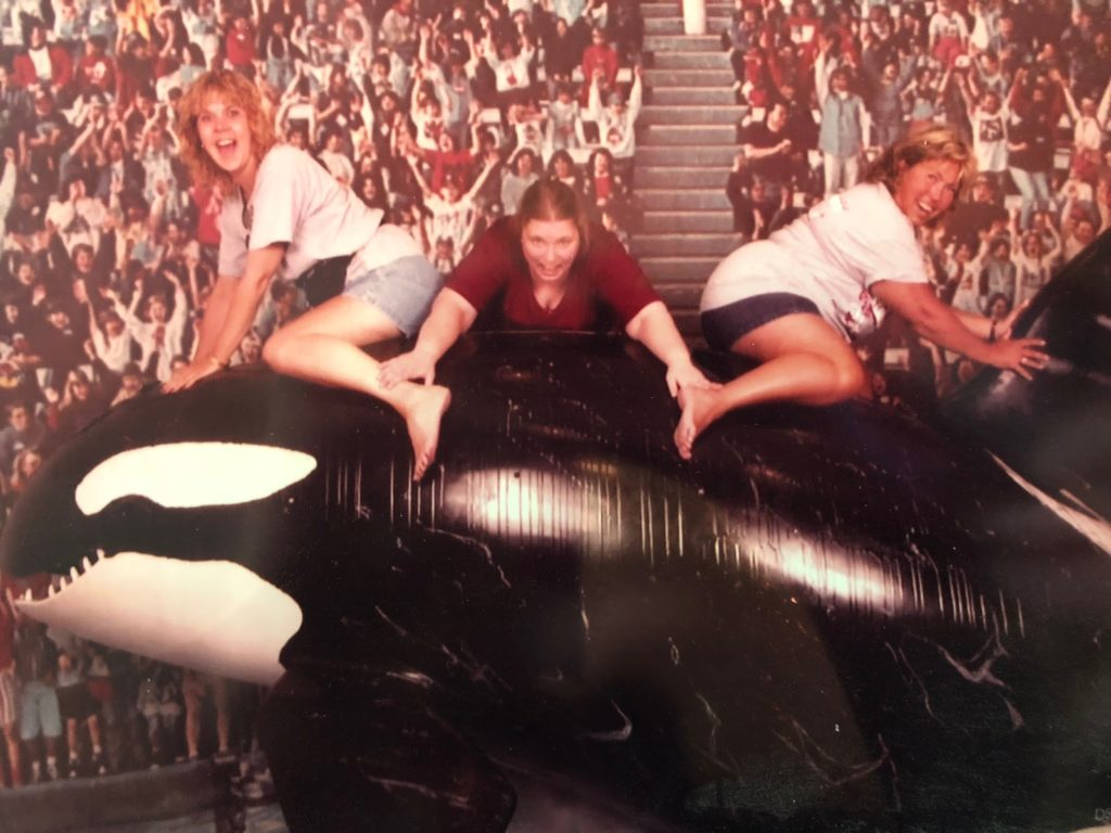 Melissa, Cathy, and Susan posing on an Orca statue